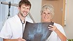 Ein Arzt und eine Ärztin halten ein Röntgenbild in den Händen
