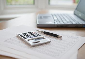 Laptop, Stift, Taschenrechner und Papiere auf den Tisch | © IA98/iStockphoto.com