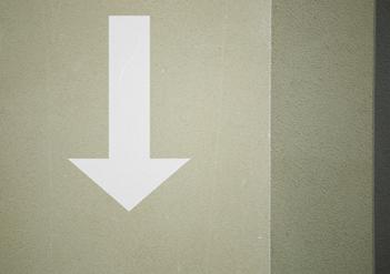 Weißer Pfeil nach unten auf beigefarbener Wand